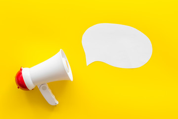 Megaphone with bubble for announcement text on yellow background top view space for text