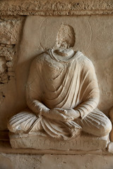 The sedentary statue of Buddha at the stupa base, Jaulian archaeological Complex, in the Khyber Pakhtunkhwa Province of Northern Pakistan