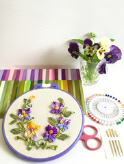Still life with embroidery of yellow and violet pansies and flowers on a white table. Sets of pins, needles and colorful satin ribbons (the embroidery made the author of photo)