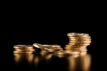 The concept of deposit accumulation, the concept of money growth. Scattered coins. Stack of gold coins on a black background. Fototapete