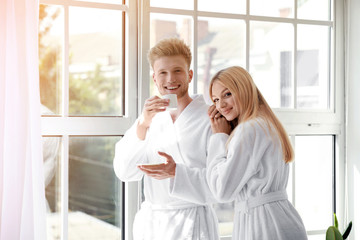 Wall Mural - Morning of happy young couple in bathrobes near window