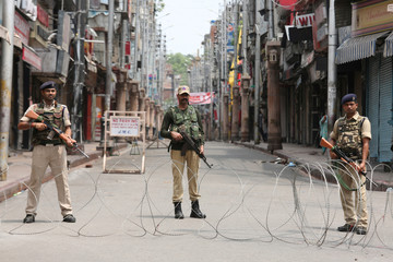 Indian security personnel stand guard along a deserted street during restrictions in Jammu