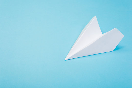 Flat lay of white paper airplane and blank paper on blue background.