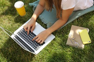 Female blogger with laptop lying on grass in park Fototapete
