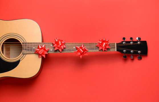 Guitar and Christmas decor on color background