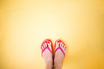 Woman's legs wearing pink flip flops on yellow background with copy space
