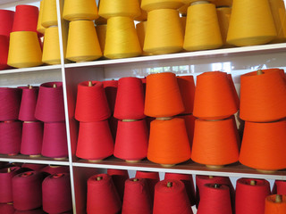 collection of spools of thread in orange, yellow, red and purple;