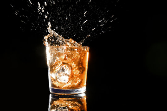 Splash of whiskey in glass on dark background
