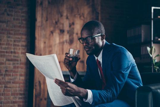 Photo of dark skin macho guy sitting office sofa drinking alcohol beverage reading fresh press wear elegant costume