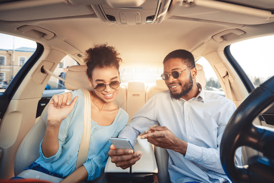 African-american couple using navigator app on phone in car