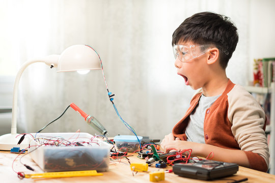 Smart looking preteen / teenage Asian boy wowing with mouth open wide successfully repairing, solid state relay in laboratory, wearing protective / safety glasses. Electronics, Sciences school project