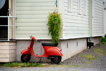 Old vintage red scooter by the wooden house in Finland