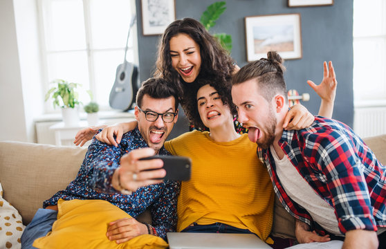 A group of young friends with smartphone sitting on sofa indoors, taking selfie.