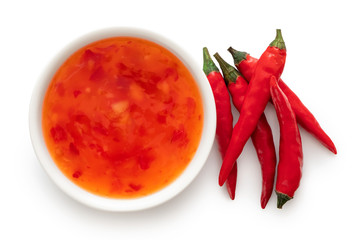 Sweet chilli sauce in a white ceramic bowl next to a pile of red chillies isolated on white from above. Wall mural