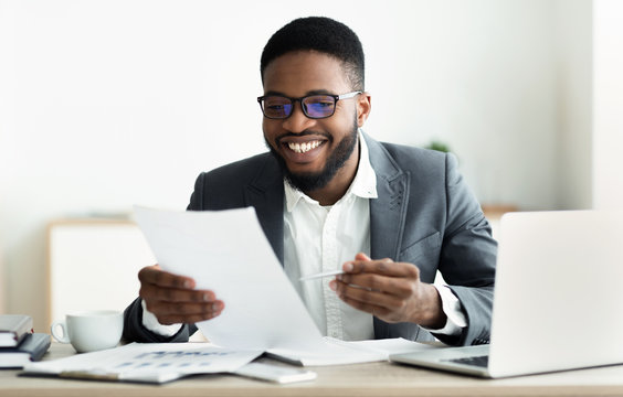 Smiling black businessman checking reports in modern office