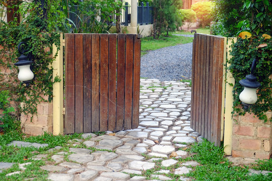 Opening wood gate to the outside stone walkway