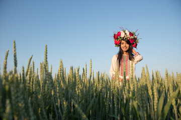 Pretty young indian woman wear traditional Ukrainian clothes and flower wreath walk in wheat field, beautiful ethnic girl in handmade decorated floral crown admire nature, blue sky background Wall mural