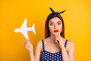 Close-up portrait of her she nice attractive puzzled confused straight-haired girl holding in hands white plane decide decision one way isolated over bright vivid shine yellow background Fototapete