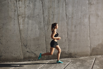 Jogging, endurance and sport concept. Side shot fit sporty young woman in activewear running near concrete wall into sun, daily training and morning exercises, sportswoman training to run marathon Fototapete