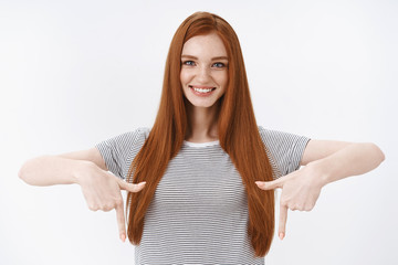 Good-looking confident redhead girl straight ginger hairstyle wearing summer striped t-shirt pointing index fingers down smiling self-assured giving advice showing awesome best product must have