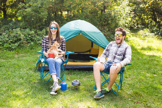 people, summer tourism and nature concept - young couple sitting near a tent