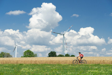 nice, active woman, riding her electric mountain bike between wheat fields and wind wheewls of a wind farm on the Schwaebische Alb near the city of Aalen, BadenWuerttemberg, Germany