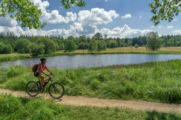 nice senior woman, riding her electric mountain bike along the Weiherwiesen Lake, a biotope on the Swabian Alb near Heubach, Baden-Wuerttemberg, Germany