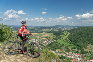 nice senior woman with electric mountain bike, looking from view on the Swabian Alb down to the wide plains of Baden Wuerttemberg, Germany