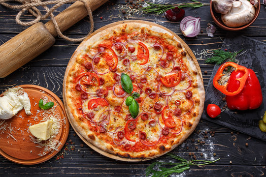 Aromatic pizza with hunting sausages, onions and tomatoes