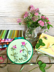Still life with embroidery satin ribbons of clover flowers and bouquet of fresh clover plants on a wooden table. Sets of colorful ribbons for hand embroidery (the embroidery made the author of photo)