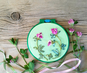 Needlework. Satin ribbon embroidery floral ornament of pink clovers and fresh  flowers on a wooden background. Flat lay, copy space, close up, still life (the embroidery made the author of photo)