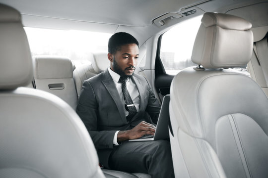 Handsome businessman working on laptop in car