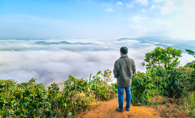 Silhouette of man standing on a high hill scenic rural hometown in the morning valley fog shrouded mountains looming large undulating scenic spot