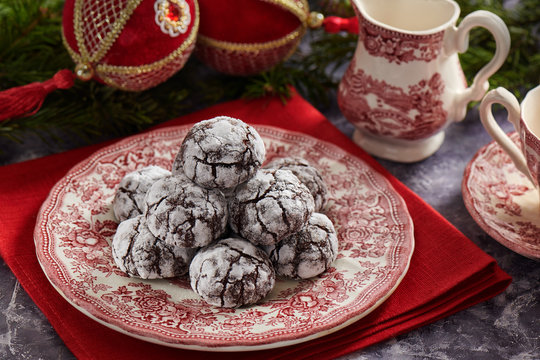 Pile of cracked chocolate cookies on old english style plate, Christmas decoration on background