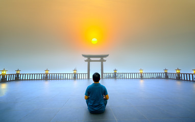 Silhouette of man in meditation posture temple near Bao Loc, Vietnam. All settled as a way to relax soul into realm of spiritual peace deposition where Buddha door in morning