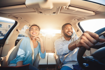 Enjoying travel. Excited african couple driving car