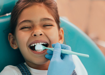 Cute little girl getting teeth exam at dental clinic