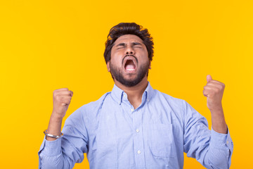 Young Indian brunette male rejoices posing on a yellow background. Concept of success and win.