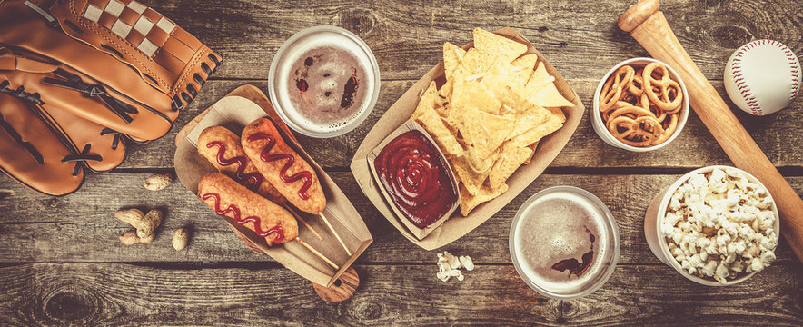 Selection of stadium game foods - nachos, pop corn, pretzels, corn dogs, rustic wood background