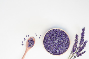 Tuinposter Lavendel Lavender flowers in wooden plate and spoon, branches on white background, toned. Spa, recipe concept. Top view, close-up, flat lay, copy space, layout design