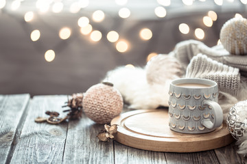 Coffee cup over Christmas lights bokeh in home on wooden table with sweater on a background and decorations. Holiday decoration, magic Christmas
