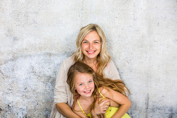 pretty, blonde young mother poses and cuddles with her daughter in front of a concrete wall and...