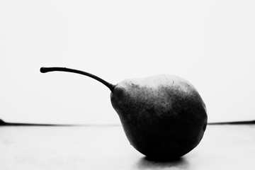 black and white still life of one pear lies on a tiled table
