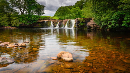 Wain Wath Force on the River Swale, is a waterfall situated on the River Swale in the Yorkshire Dales National Park and flows beneath the limestone cliffs of Cotterby Scar