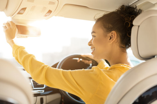 Happy girl touching rear view mirror, driving car