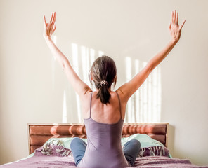 Back view of a Caucasian woman waking up in bed and stretching her arms with copy space