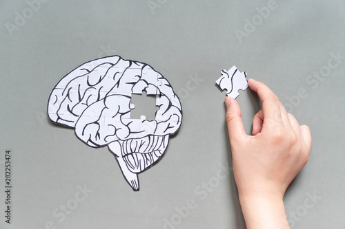 Wall mural Female hand trying to connect a missing jigsaw puzzle of human brain on gray background. Creative idea for solving problem, memory loss, dementia or Alzheimer's disease concept. Mental health care.
