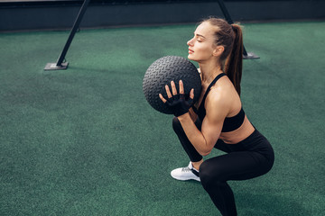 Side view of woman squatting with a medicine ball outdoors