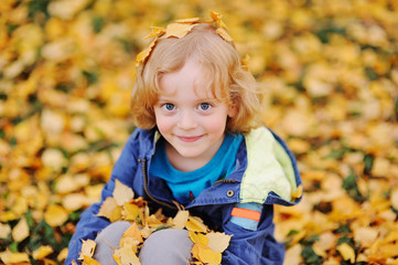 baby - little boy with curly blond hair smiling against the background of yellow autumn leaves in the Park
