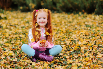 little cute red-haired girl child with yellow fallen leaves on her hair smiling against the autumn leaves in the Park.space for text, copy space,
